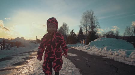 buty : A little cute girl in a pink jumpsuit runs through the puddles in the snow on a clear sunny evening at sunset, slow motion.