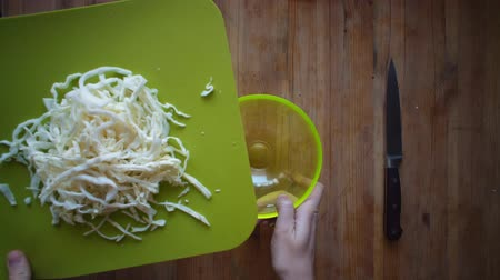 picado : Top view of female hands pouring slices of white cabbage from a green cutting board into a glass plate, close up. Stock Footage