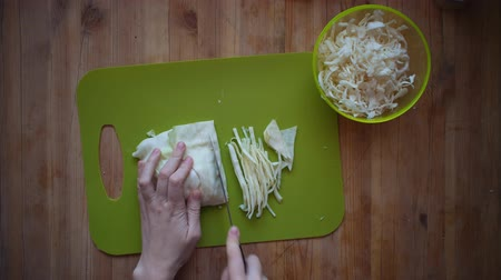 picado : Top view of female hands chopping white cabbage with a kitchen knife on a green cutting board, close-up. Stock Footage