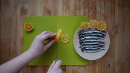 sprat : Top view of a process of male hands cutting a lemon into round flat slices of a knife on a green cutting board, then decorating the small fish in a beige plate on a wooden table with pieces. Stock Footage