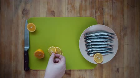 sprat : Top view of the process of making a small silver fish, male hands cover capelin with fresh lemon slices, lying in a beige plate on a wooden table.