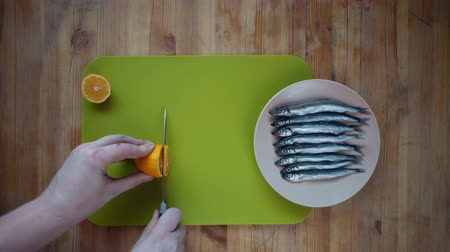 sprat : Top view of a process of male hands cutting a lemon into round flat slices of a knife on a green cutting board, next to a small fish in a beige plate on a wooden table. Stock Footage