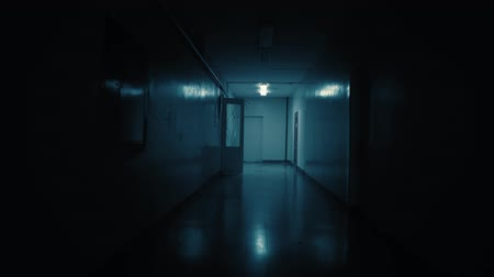 włamywacz : Tracking inside a long dark gloomy corridor. A dark silhouette of a girl dressed in a parka stops in front of the camera.White big clocks hang on the wall and show ten to eleven.Concept of horror. Wideo