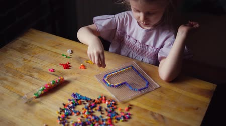 puzle : Handheld shot of little cute caucasian girl makes colorful decoration in shape of heart from mosaic. Child sits at wooden table and prepares gift for day of mother, father or valentine. Wideo