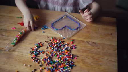 mateřská škola : Handheld shot of little cute caucasian girl makes colorful decoration in shape of heart from mosaic. Child sits at wooden table and prepares gift for day of mother, father or valentine. Dostupné videozáznamy
