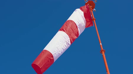 velocímetro : Windsock with red and white stripes develops on blue cloudless sky background. Weathersock show direction of wind blowing and speed. Cone equipped floodlights on top surrounding it.