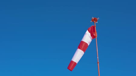 indicar : Windsock with red and white stripes develops on blue cloudless sky background. Air sock show direction of wind blowing and speed. Cone equipped floodlights on top surrounding it.