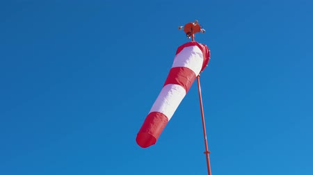 meteorologia : Windsock with red and white stripes develops on blue cloudless sky background. Wind sock show direction of breeze blowing and speed. Cone equipped floodlights on top surrounding it.