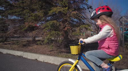 педаль : Camera follows little cute blond girl in protective helmet and pink vest, she rolls on blue bicycle with yellow basket in old park.