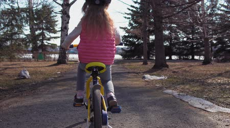 gyerekes : Handheld back view shot of five-year-old little blonde girl in red protective helmet ride bike on asphalt track with gaps and holes sunny day in old park. Stock mozgókép