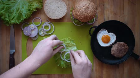 houska : Top view of the process of cooking a burger right above the wooden table. Male hands put burger ingredients on a bun, doubts and removes everything from the bread.