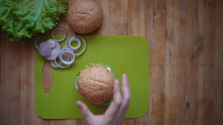 houska : Flat lay of the process of cooking a burger overhead view the wooden table with ingredients and male hands. Male hands put a sesame bun on the finished hamburger and pierce with a stick.