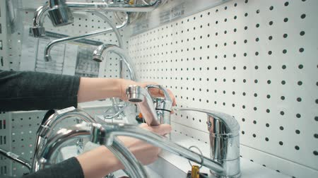 encanador : Close up of female hands rotate handle and switching mixer tap of exhibition sample, checking its quality. Young caucasian woman chooses water faucet in sanitary engineering shop. Stock Footage