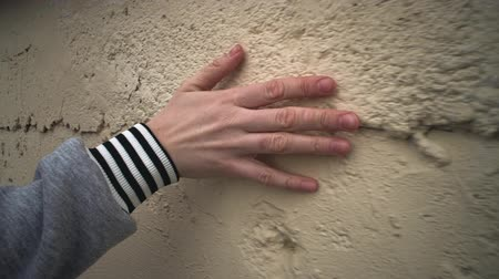sıva : Camera follow close up of human hand touches yellow plastered wall, fingers stroking rough, uneven surface of building.