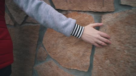 sentido : A woman walks next to a beige rock wall and touches her surface with her hand, handheld shoot.