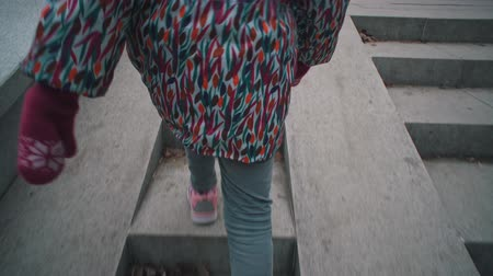 tread : View back handheld shoot of little girl in pink sneakers climbs stone steps in dry leaves. Child walks on gray stairways in city park.