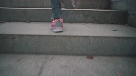 lépcsőház : View back camera follow of little girl in pink sneakers climbs stone steps in dry leaves. Child walks on gray stairways in city park. Stock mozgókép