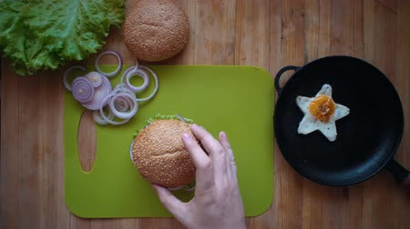 egg laying : Top view of the process of cooking a burger right above the wooden table. Male hands put a bun with sesame seeds on the ready hamburger.