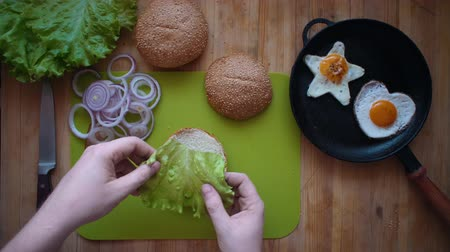 egg laying : Top view of the process of cooking a burger right above the wooden table. Male hands put a green leaf of lettuce on a hamburger bun. Stock Footage