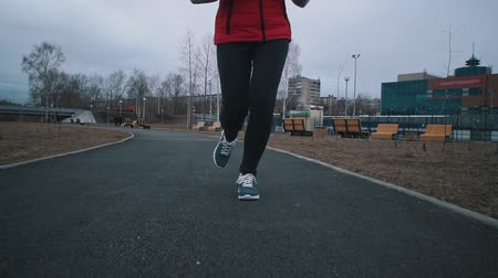 women's : Camera follows front view of womens legs in dark leggings and gray sneakers with white laces run along the paths of the public park on a cloudy day, slow motion.