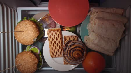 ataque : Top view on the shelf of the refrigerator. Someone puts a sweet bun on a red plate. Irregular nutrition and sleep disturbance.
