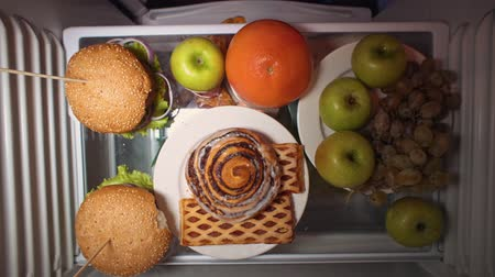grejpfrut : Top view on the shelf of the refrigerator, the battle for food. A womans hand wants to take pastries, but mens fingers point to a grapefruit. Wideo