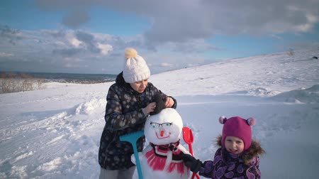 snow caps : Mother and daughter together making snowman. Happy young family playing in fresh snow at winter day outdoor in mountain with cloudy sky in background. Stock Footage