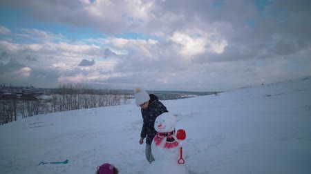 kardan adam : Mother and daughter together making snowman. Happy young family playing in fresh snow at winter day outdoor in mountain with cloudy sky in background. Stok Video