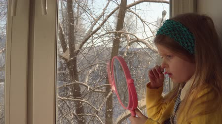 mustard : Little cute girl in a mustard cardigan and a blue bandage puts makeup looking in a pink mirror, she sits on the windowsill, outside the window is a winter landscape. A child learns to use cosmetics. Stock Footage