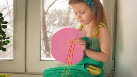 varrónő : Cute little girl sews a handbag. The child learns to use a needle and thread sitting on the windowsill on the background of snowy trees