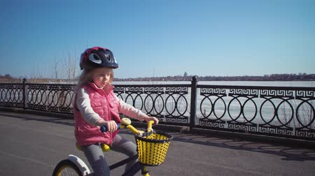 védősisak : Little blond girl in protective helmet riding blue bike on an asphalt track with gaps and holes along embankment of frozen river. Sport concept, active kid playing and cycling first bicycle outdoors.