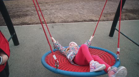 plac zabaw : Little cute girl swinging on round swing with tight weave rope platform seat in park on cloudy day.