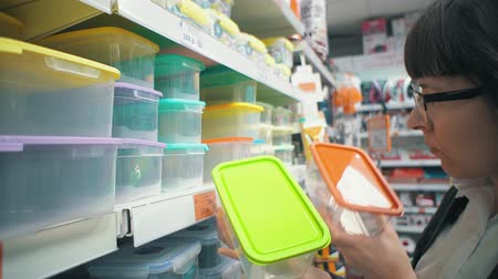 reutilizável : Young brunette woman in glasses choose a plastic container in the department with utensils in the supermarket. Girl buying reusable lunchbox. Zero waste concept.