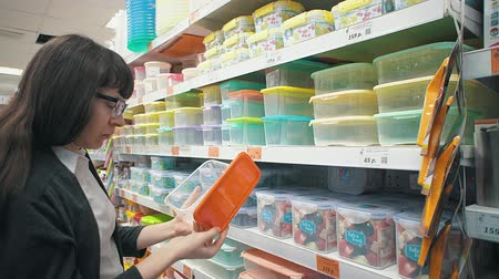 preservation : Young brunette woman in glasses choose a plastic container in the department with utensils in the supermarket. Girl buying reusable lunchbox. Zero waste concept.