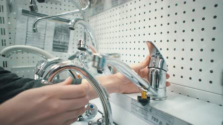 sanitair : Close up of female hands rotate handle and switching mixer tap of exhibition sample, checking its quality. Young caucasian woman chooses water faucet in sanitary engineering shop. Stockvideo