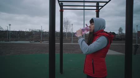 recyklovat : Sportswoman in red sleeveless jacket drinks water of reusable plastic bottle on sports field in cloudy day.