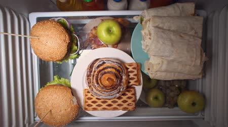 grejpfrut : Top view on the fridge shelf, the problem of choosing between healthy and unhealthy food, someone takes a sweet bun instead of an green apple at night. Irregular nutrition and sleep disturbance.