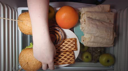 shoarma : Top view on the shelf of the refrigerator, the problem of choosing between healthy and unhealthy food, someone takes a grapefruit instead of sweet pastries at night.