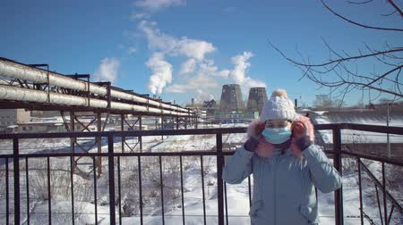 węgiel : Portrait of a young woman in a protective mask and gray park against the background of the pipes of the metallurgical plant on a winter day.