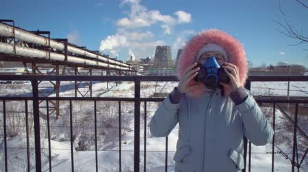 ısıtma : Portrait of a young woman in a protective mask and gray park against the background of the pipes of the metallurgical plant on a winter day.