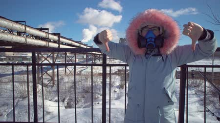 contaminação : Portrait of a young woman in a protective mask and gray park against the background of the pipes of the metallurgical plant on a winter day. Young woman showing thumbs down.
