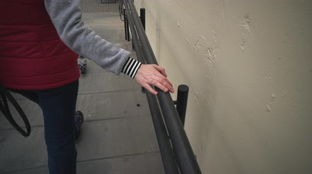 sıva : A young woman in a red jacket walks and touches a metal black railing with her hand. The girl comes down the stairs next to the yellow plastered wall. Stok Video