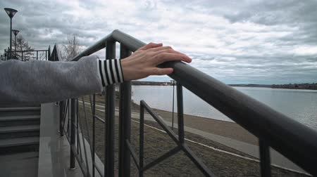 handrails : A young woman in a red jacket walks and touches a metal black railing with her hand. A girl climbs the stairs upstairs near the embankment of the rocky river on a cloudy day. Stock Footage