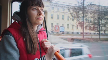 daily : Young brunette woman in red sleeveless jacket stand in tram and looks out window while riding in public transportation.