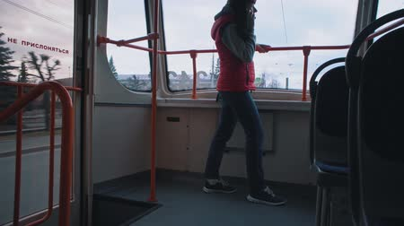 söylemek : Woman stand in tram, holding the handle and using mobile phone. Happy female passenger speaks on smartphone while riding in public transportation. On-year window written on russian not lean against. Stok Video