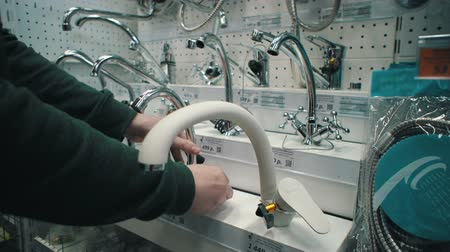 потребитель : Close up of male hands rotate handle and switching ceramic mixer tap of exhibition sample, checking its quality. Young caucasian man chooses water faucet in sanitary engineering shop.
