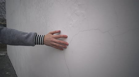percepção : Camera follow close up of human hand touches white plastered wall, fingers stroking rough, cracked surface of building. Stock Footage