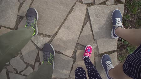幼稚な : Top view of three pairs of legs, male childish and female foots in shoes stepping along stone road. Kid strolls between his parents in red sneakers. Dad daughter and mom go together, family concept.