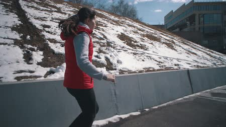склон холма : Handheld shot side view of sportswoman performs cardio while doing a jogging. Athletic brunette girl in red sleeveless jacket runs along road next to the snow-covered hillside on clear winter day.