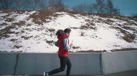 склон холма : Handheld shot side view of sportswoman in headphone engaged in sports. Athletic brunette girl in red sleeveless jacket runs along road next to the snow-covered hillside on clear winter day.